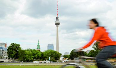 Person riding a bicycle near Alexanderplatz, Berlin, Germany with television tower in the background.