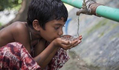 A village boy drinking water from the community based Rain Water Storage Plant of Lighthouse Project at Patharghata in Barguna district, Bangladesh